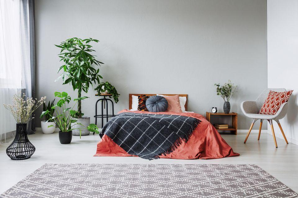 Schlafzimmer gemütlicher machen: Bett umringt von Pflanzen