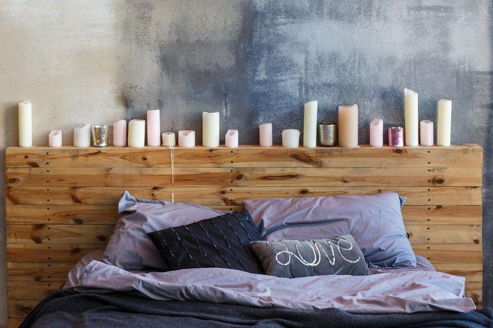Schlafzimmer gemütlicher machen: Holzregal mit Kerzen am Kopfende des Bettes