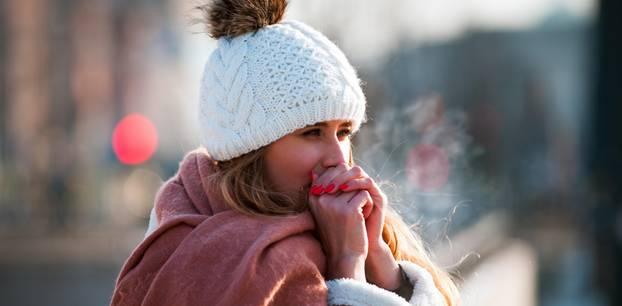 Kälte verschlimmert Krankheiten: Frau friert draußen in der Kälte