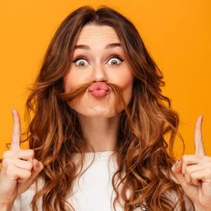 Damenbart entfernen: Frau mit langen Haaren und Haarsträhne als Schnäuzer