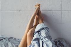 Apfelstrudel-Stellung: Frauenbeine und Männerbeine gucken unter der Bettdecke hervor