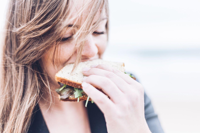 Das Brigitte-Balance Konzept: Frau beißt in Sandwich