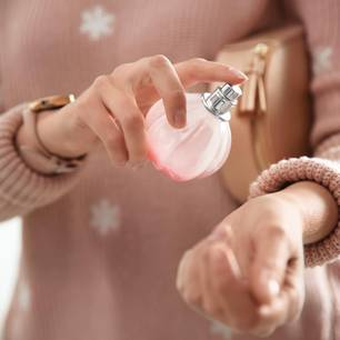 Parfum: Frau sprüht sich einen Duft auf