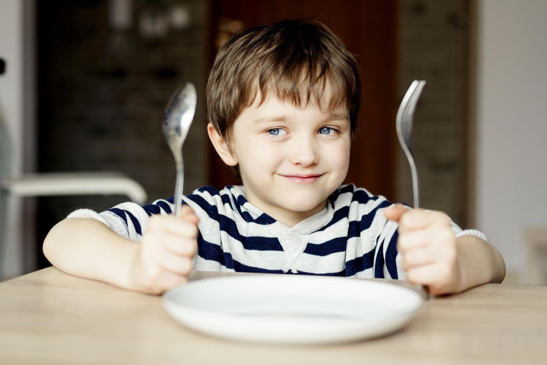 Tipps, wie Kinder Warten lernen: Junge wartet brav vor leerem Teller auf sein Essen
