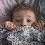 10 Kinderängste und 5 Lösungen: Junge schaut ängstlich unter der Bettdecke hervor