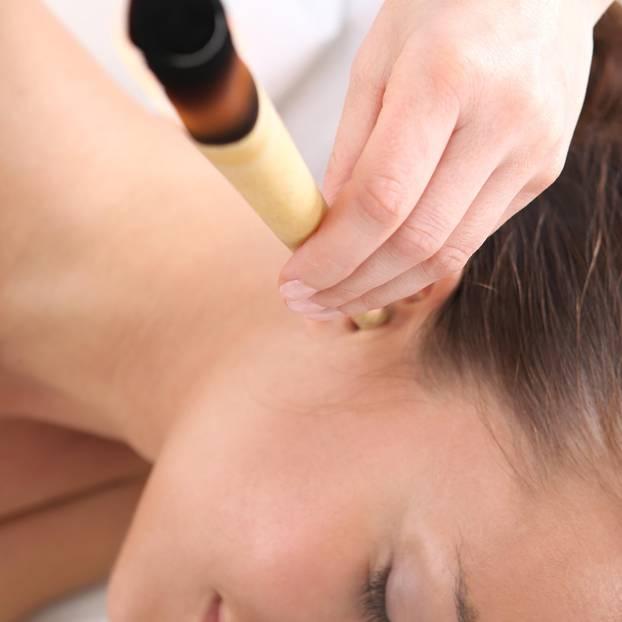 Ohrenkerzen Anwendung: Frau hält Ohrenkerze ins Ohr