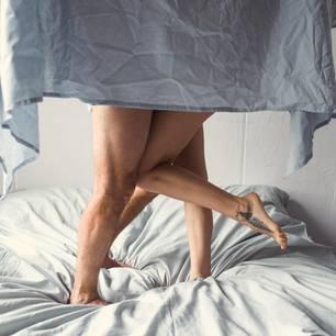 Warum du vor dem Sex nicht duschen solltest: Frau und Mann im Bett
