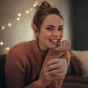 Frau mit Kaffee lächelt