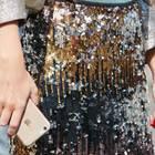 Silvester-Outfit: Frau mit Pailettenrock und Smartphone in der Hand