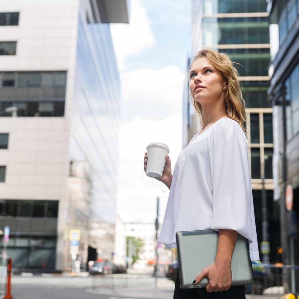 Berufliche Neuorientierung: Frau mit Akten vor einem Unternehmen