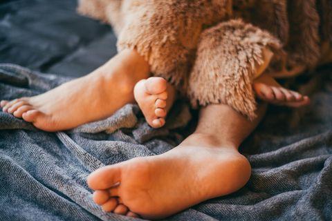 Sexsomnia: Zwei ineinander verschränkte Fußpaare schauen unter der Bettdecke hervor