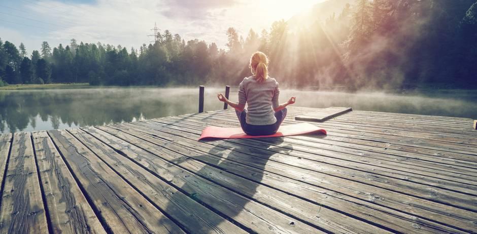 Stille ist gut für das Gehirn: Frau meditiert an See