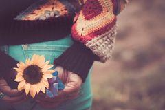 Gretchen Rubin: Eine Frau in einem Strick-Pulli von hinten mit einer Sonnenblume in der Hand