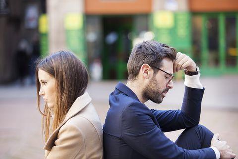 Beziehungs-Wahrheiten, die niemand gerne sagt: Pärchen sitzt Rücken an Rücken schweigend zusammen