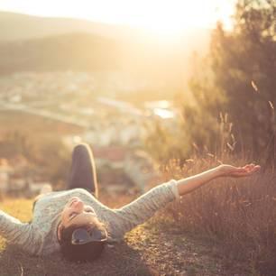 Dinge, zu denen man öfter Nein sagen sollte: Eine junge, sorglose Frau liegt auf einem Hügel in der Abendsonne