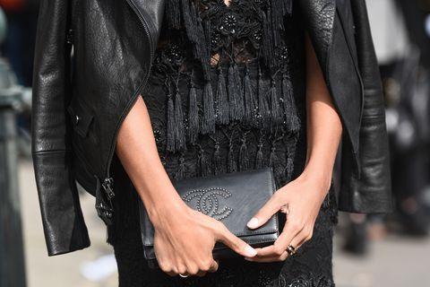 Silvester-Outfit Inspiration: Frau mit schwarzer Handtasche in den Händen und Lederjacke