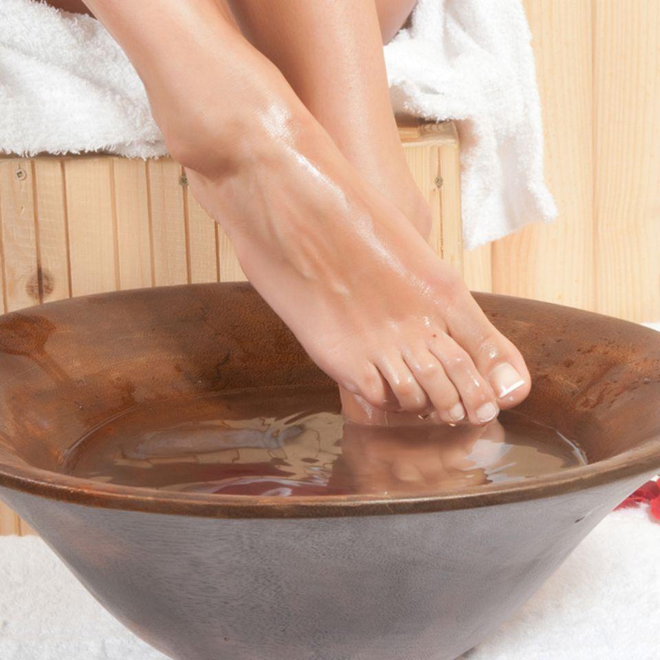 Nagelbettentzündung: Hausmittel zur Behandlung: Frau hält ihre nackten Füße in eine Schüssel mit Wasser