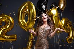Beauty-Vorsätze 2019: Frau im goldenen Pailettenkleid mit Luftballons in der Hand