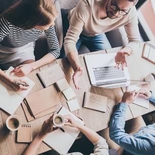 Brainwriting: Arbeitsgruppe diskutiert am Tisch