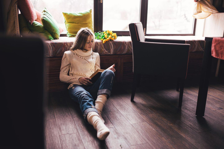 Single-Gen: Eine junge Frau sitzt allein auf dem Boden und liest ein Buch