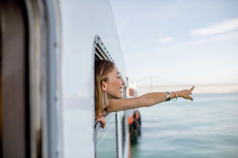 Emotionale Intelligenz: Eine junge Frau auf einem Schiff zeigt auf den Ozean