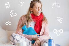Diese Sternzeichen sind die größten Hypochonder: Eine Frau mit Wärmflasche auf dem Bauch und Fieberthermometer im Mund