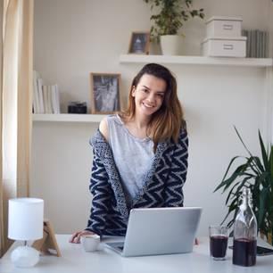 Geld verdienen von zu Hause – was ist möglich? Junge Frau steht am Schreibtisch in ihrer Wohnu, vor ihr ein aufgeklapptes Laptop