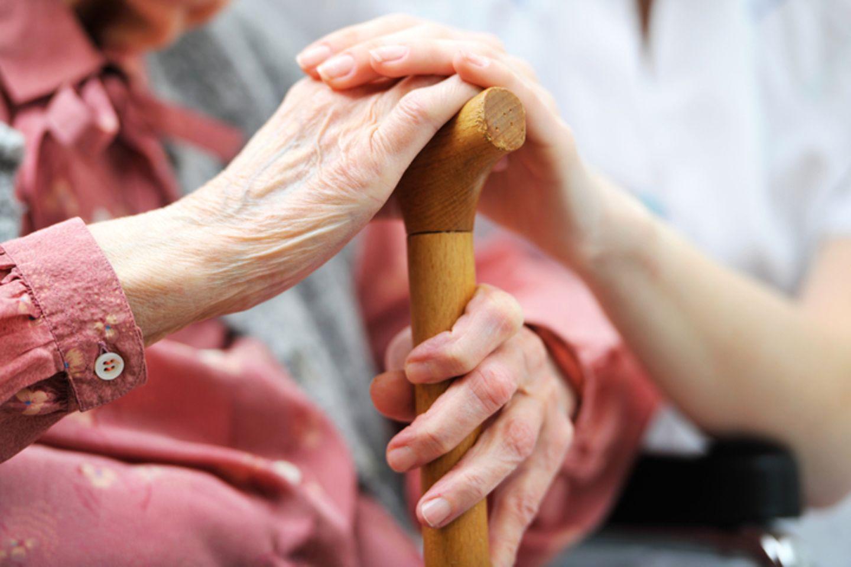 Pflegerin streichelt Hand einer alten Frau