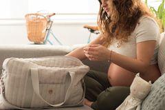 Kliniktasche: Schwangere Frau packt Tasche