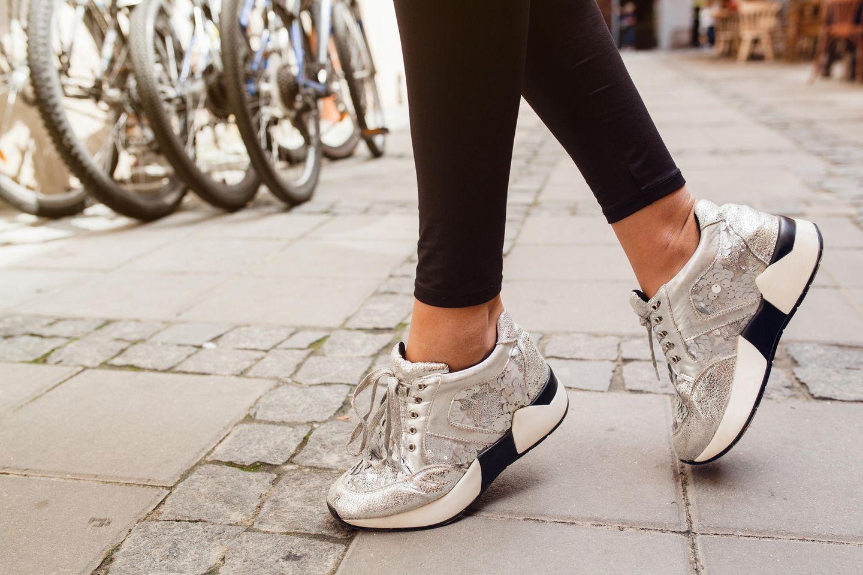 Sneaker-Trends 2019: Frau mit silbernen Sneakern und schwarzer Hose