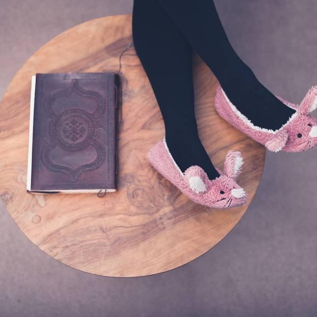Selbstakzeptanz: Füße in Plüschpantoffeln, die auf einem Tische liegen