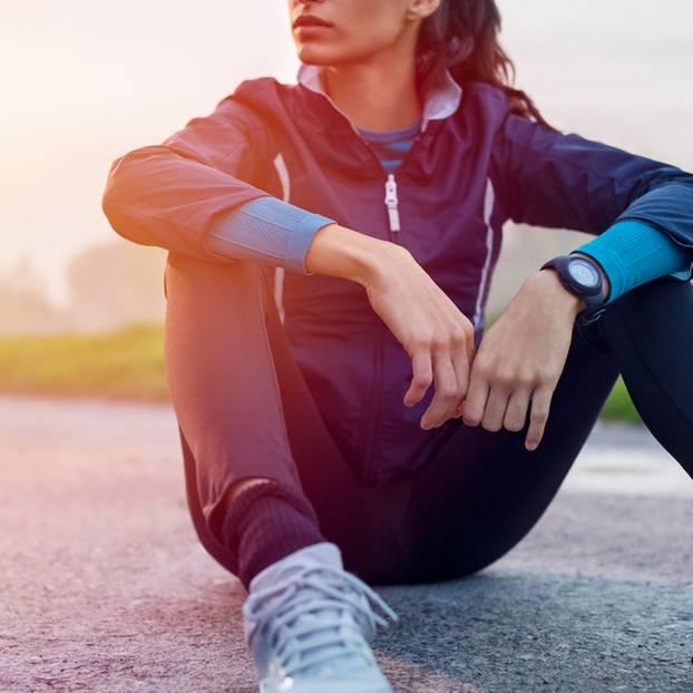 Abschied vom Lieblingssport: Frau sitzt in Sportkleidung auf dem Boden