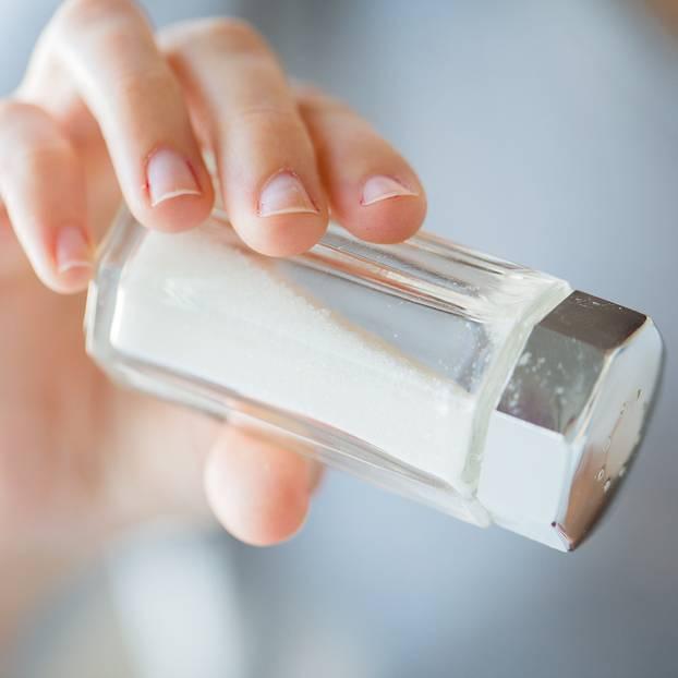 Frauenhand hält Salzstreuer
