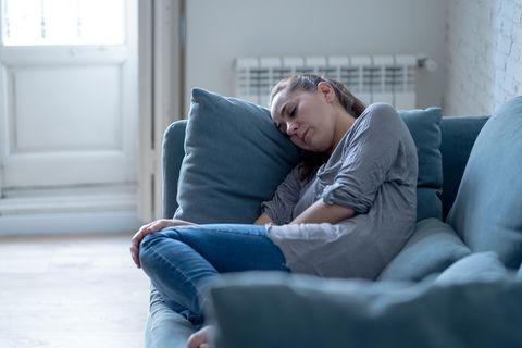 Übelkeit: Junge Frau sitzt auf dem Sofa