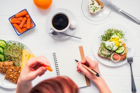 Ernährungsplan erstellen: Frau mit Notizblock am Küchentisch