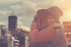 Emotionale Affäre: Mann und Frau umarmen sich vertraut auf einem Hausdach