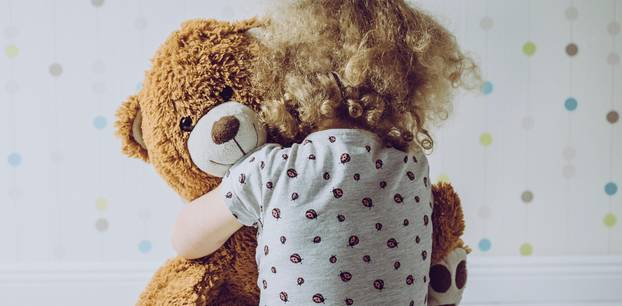 Wie gewöhnt man seinem Kind das Kuscheltier ab? Kleines Mädchen umarmt Teddybär