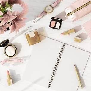 Büro-Essentials: Schreibtisch mit Notizheft, Lippenstift, Puder und Lidschatten