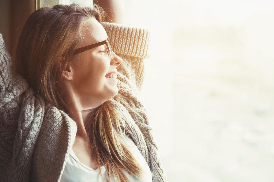 Einfache Tricks, um glücklich zu sein: Eine zufriedene junge Frau lehnt sich entspannt zurück