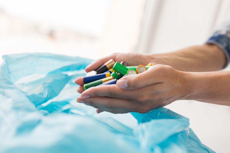 Batterien entsorgen: Batterien werden in Müllsack gelegt