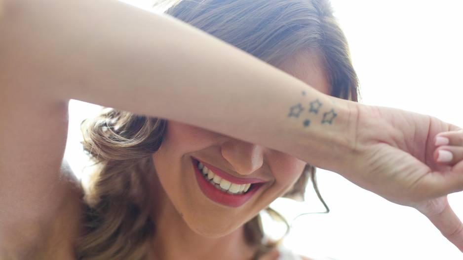 Umfrage: Eine Frau verdeckt lachend ihr Gesicht
