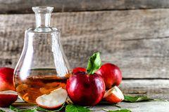 Apfelessig selber machen in wenigen Schritten: Karaffe mit Apfelessig und roten Äpfeln daneben