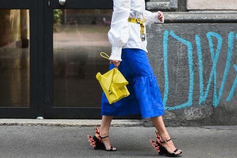 Lemon Verbena: Frau mit gelber Tasche und blauem Rock