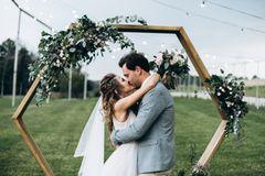 Hochzeitstrends 2019: Diese 6 werdet ihr lieben: Hochzeitspaar küsst sich vor einem geschmückten Holzbogen