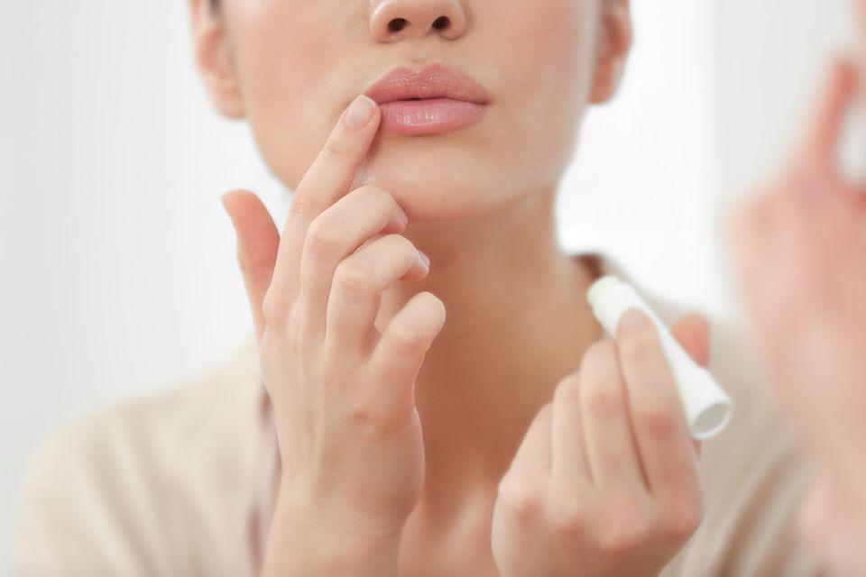 Lippenpflege: Frau trägt Lippenpflegestift auf
