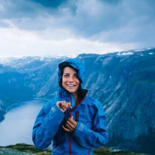 Regenjacke imprägnieren – mit diesen Tipps klappt's! Frau steht in Regenjacke vor einer Berglandschaft