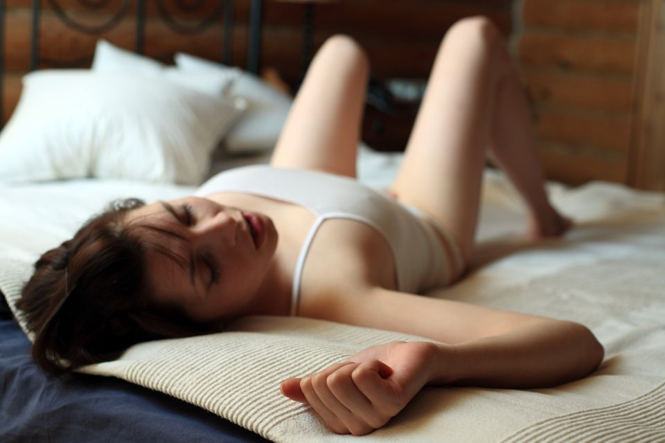 Selbstbefriedigung: Frau auf Bett