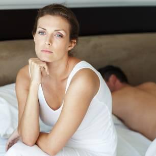Innere Unruhe: Frau neben schlafendem Mann