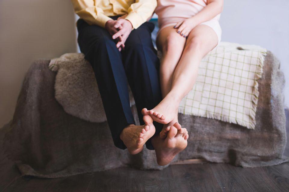 Körpersprache, die Beziehungsende andeutet: Pärchen sitzt auf dem Bett mit verschränkten Füßen