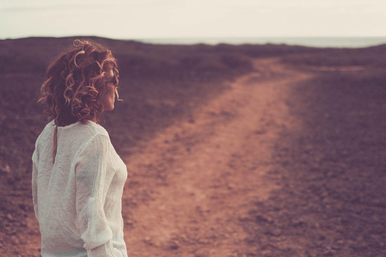 Rückführung: Frau steht auf einem Feldweg
